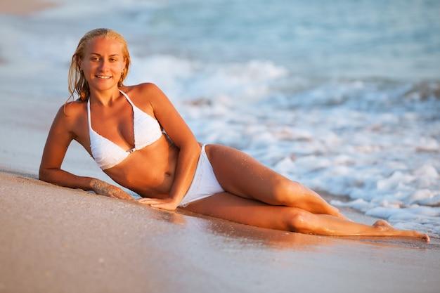 Schöne junge blonde frau im weißen bikini, der auf sand nahe meerwasser liegt