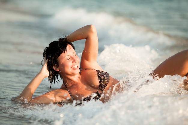 Schöne junge blonde frau im weißen bikini, der auf sand nahe meerwasserrand liegt und sonnenschein am sonnigen sommertag genießt. familienurlaub und reisekonzept