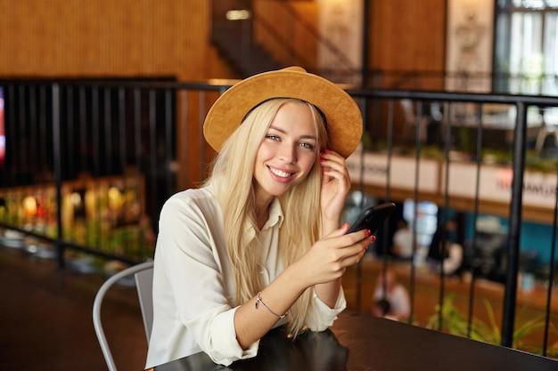 Schöne junge blonde frau mit dem langen haar, das hut und weißes hemd trägt, sitzt am tisch über caféinnenraum und schaut mit aufrichtigem lächeln