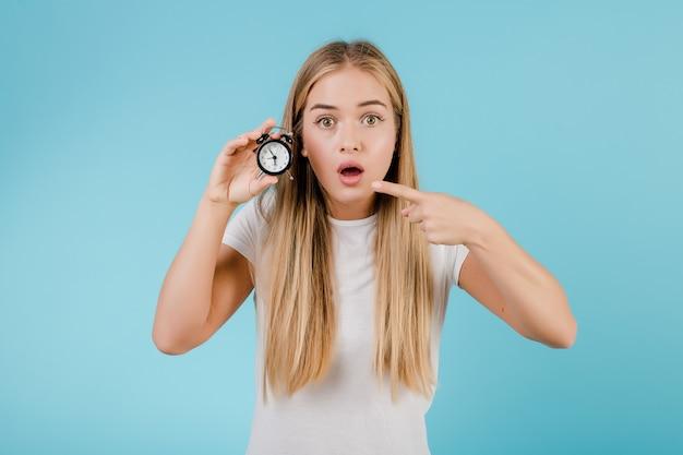 Schöne junge blonde frau mit der alarmuhr, welche die zeit getrennt über blau zeigt