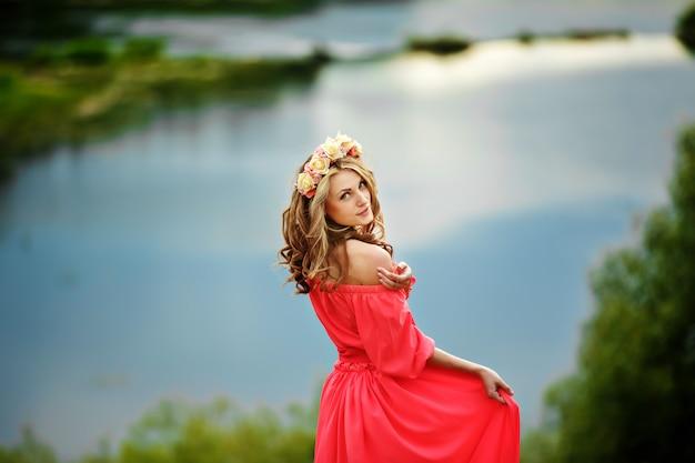 Schöne junge blonde frau mit einem blumenkranz auf ihrem kopf. schönheitsmädchen mit blumenfrisur in einem roten langen kleid nahe dem see.