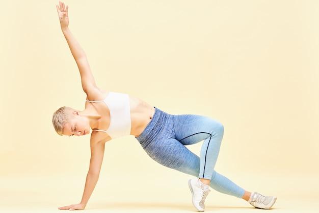 Schöne junge blonde frau mit herrlichem muskulösem körper, der auf gleichgewicht und kraft arbeitet, die seitenplanke oder vasisthasana-pose tut, die einen arm hebt und versucht, das gleichgewicht so lange wie möglich aufrechtzuerhalten