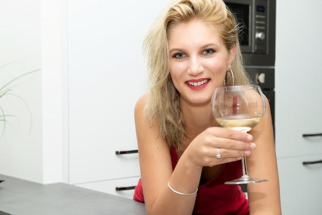 Schöne junge blonde frau mit rotem kleidertrinkendem weißwein