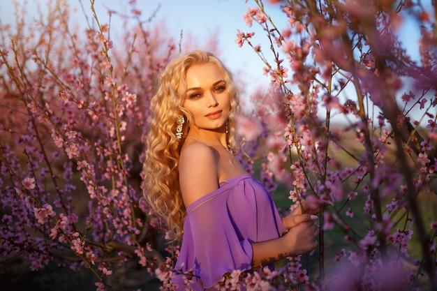 Schöne junge blonde frau mit welligem haar, das mit blühenden pfirsichbäumen gegen den himmel aufwirft.