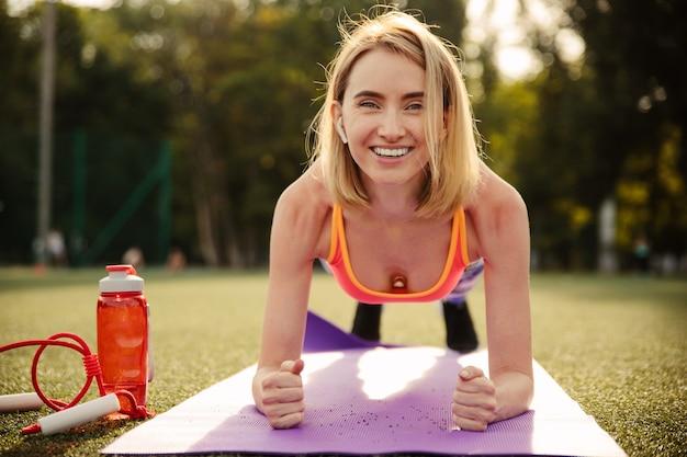 Schöne junge blonde lächelnde frau, die sportkleidung trägt, die plankenübung auf einem sportfeld tut
