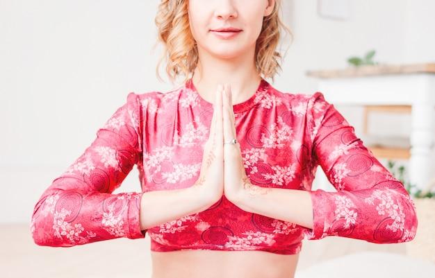 Schöne junge blonde lächelnde frau in übendem yoga asana namaste des roten ethnischen kostüms