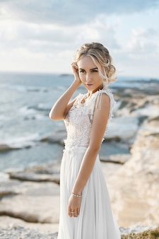Schöne junge blonde modellfrau mit nacktem make-up in einem modischen hochzeitskleid, das an der seeküste bei zypern geht