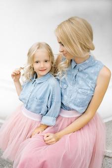 Schöne junge blonde mutter und ihre charmante tochter in den gleichen romantischen kleidern.