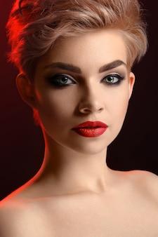 Schöne junge blonde rote lippige frau auf rotem hintergrund.