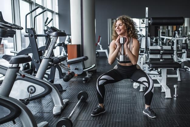 Schöne junge blonde sportlerin steht und macht kniebeugen im fitnessstudio mit hantel