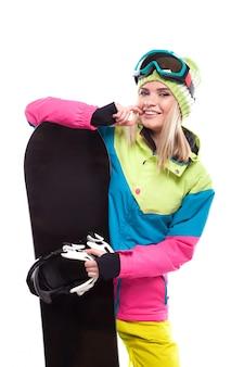 Schöne junge blondine im bunten schneemantel-griffsnowboard