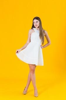 Schöne junge blondine im netten frühlingskleid, werfend auf gelbem hintergrund im studio auf