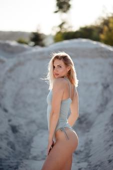 Schöne junge blondine im trendigen badeanzug, die an heißen sommertagen im sandsteinbruch steht. mode-modell mit schlankem und sexy körper, der an der frischen luft posiert.