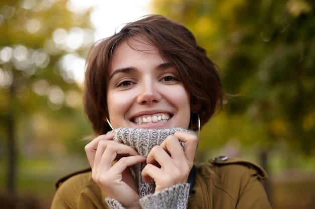 Schöne junge braunäugige brünette frau mit bob-frisur, die hände zu ihrem grauen poloneck erhebt und fröhlich mit breitem aufrichtigem lächeln schaut und über verschwommenem park aufwirft