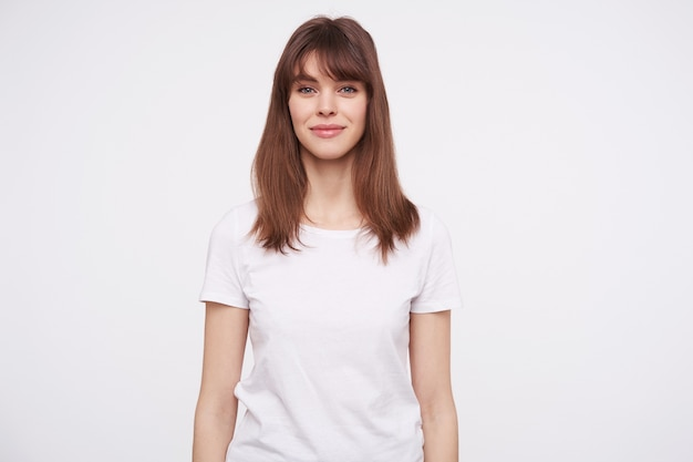 Schöne junge braunhaarige frau, die mit charmantem lächeln positiv aussieht und einfaches weißes t-shirt trägt, während sie über weißer wand posiert