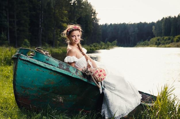 Schöne junge braut, die auf boot sitzt