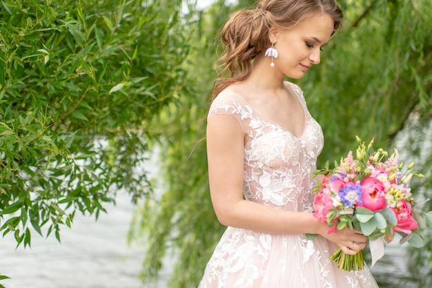 Schöne junge braut im weißen hochzeitskleid, das an natur mit blumenstrauß aufwirft.