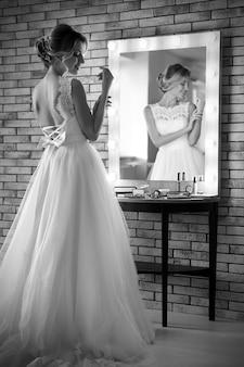 Schöne junge braut im weißen hochzeitskleid mit make-up, das vom professionellen künstler nahe spiegel innen geschaffen wird