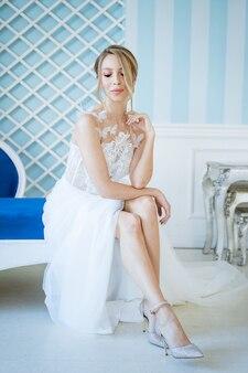 Schöne junge braut in einem weißen kleid sitzt auf dem sofa