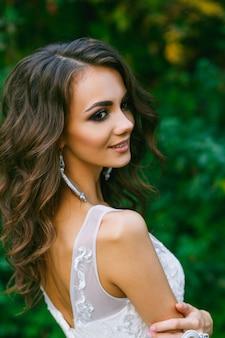 Schöne junge braut mit dem langen gelockten haar