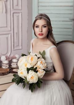 Schöne junge braut mit romantischem dekorationsrosa und -grün der blumen. holzkistenflaschen und unterschiedliche hochzeitsdekoration