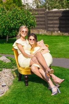 Schöne junge brautjungfern posieren zusammen auf einem stuhl