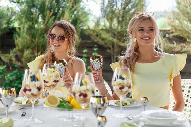 Schöne junge brautjungfern trinken champagner an einem tisch im freien