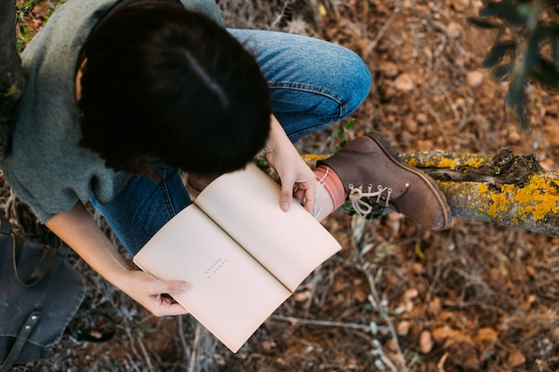 Schöne junge brünette, die auf einem gefallenen herbstlaub in einem park sitzt und ein buch liest