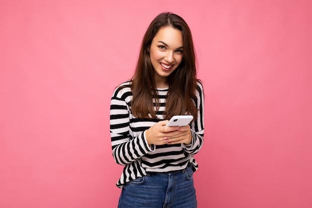 Schöne junge brünette, die handy verwendet, das über sms-nachricht trägt pullover kommuniziert