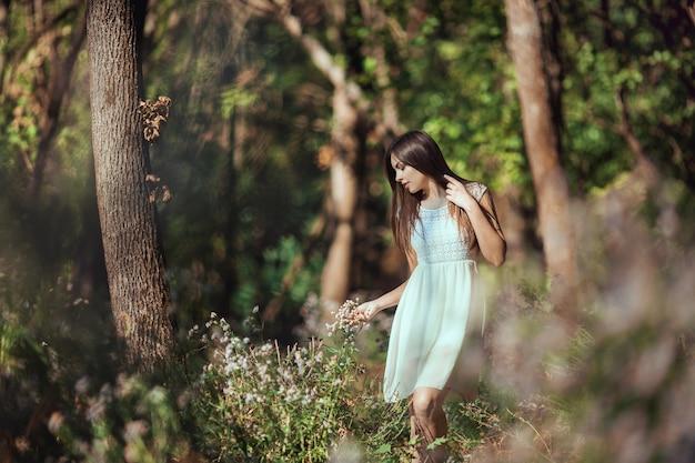 Schöne junge brünette, die im frühling auf der blühenden waldwiese geht und sich entspannt