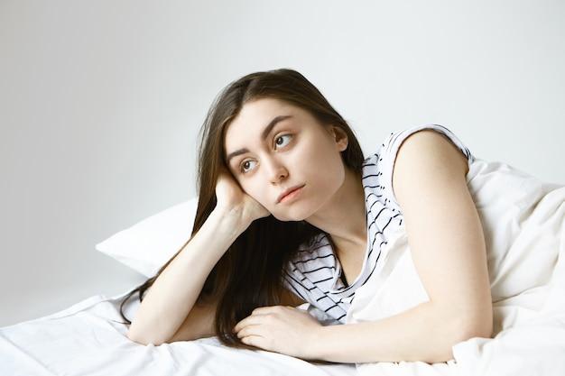 Schöne junge brünette europäische frau in gestreiften pyjamas, die sich einsam und zu tode gelangweilt fühlen, während sie im bett liegen und mit nachdenklichem gesichtsausdruck seitwärts schauen