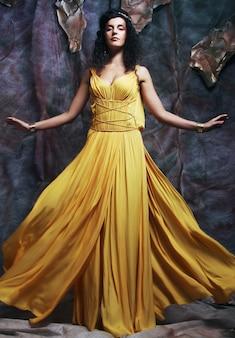Schöne junge brünette frau, die gelbes abendkleid trägt