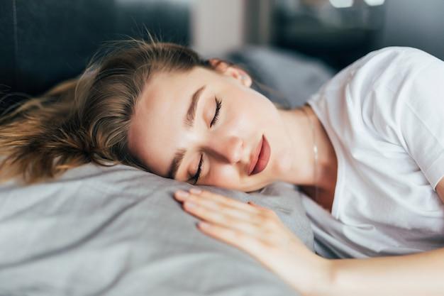 Schöne junge brünette frau, die in einem weißen bett schläft