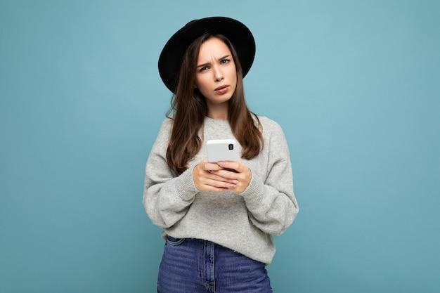 Schöne junge brünette frau, die mit schwarzem hut und grauem pullover mit smartphone denkt