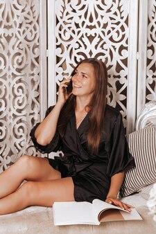 Schöne junge brünette frau im schlafzimmer spricht am telefon