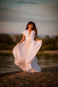 Schöne junge brünette frau in einem weißen fließenden kleid am sandstrand am abend in voller länge porträt in natürlichem licht