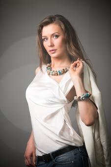 Schöne junge brünette frau in stilvoller freizeitkleidung mit ungewöhnlichen accessoires stehend
