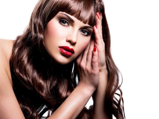 Schöne junge brünette frau mit dem langen lockigen haar, das im studio aufwirft. nahaufnahmeporträt eines weiblichen modells mit mode-make-up.