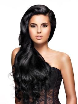 Schöne junge brünette frau mit dem langen schwarzen lockigen haar, das im studio aufwirft