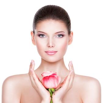Schöne junge brünette frau mit gesunder haut und rosa blumen nahe gesicht - lokalisiert auf weiß.