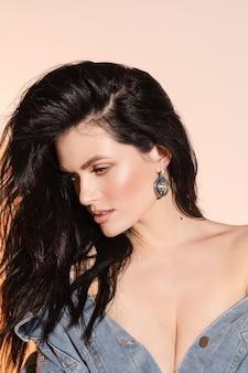 Schöne junge brünette frau mit langen gesunden haaren, perfekter haut und silbernem ohrring.