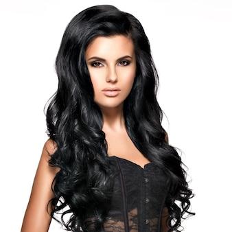 Schöne junge brünette frau mit langen schwarzen lockigen haaren posiert