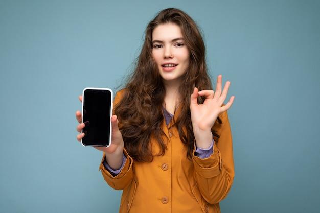 Schöne junge brünette frau mit orangefarbener jacke auf blauem hintergrund in der hand haltend