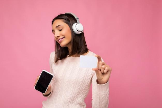 Schöne junge brünette frau mit rosa lässigen pullover isoliert über rosa hintergrundwand