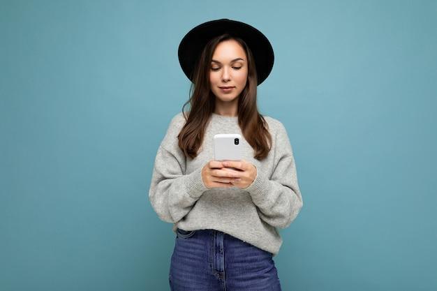 Schöne junge brünette frau mit schwarzem hut und grauem pullover mit smartphone, die auf telefon-sms einzeln auf dem hintergrund blickt.