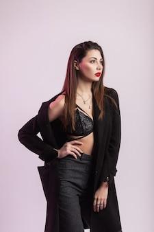 Schöne junge brünette frau mit sexy figur mit roten lippen in stylischem spitzen-bh in schwarzer mode lange jacke in trendigen gestreiften hosen posiert im studio. attraktives mädchenmodemodell im zimmer
