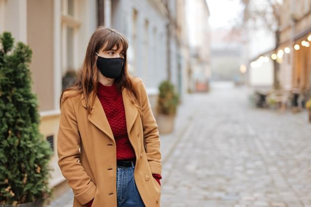 Schöne junge brünette gekleidet in der freizeitkleidung, die an der stadtstraße in der medizinischen gesichtsmaske aufwirft. konzept der grippe- und coronavirus-infektion.