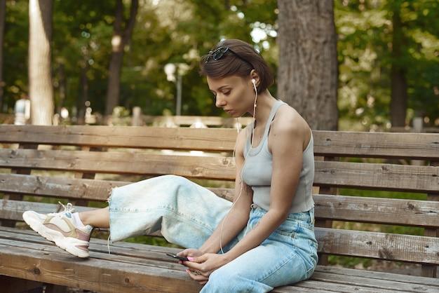 Schöne junge brünette hipsterfrau, die musik im park auf der bank hört.