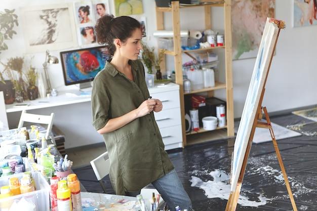 Schöne junge brünette malerin, die lässig gekleidet vor ihrem gemälde gekleidet ist, ihr bild mit bewertendem blick studiert und darüber nachdenkt, welche farben hinzugefügt werden sollen. kunst- und kreativitätskonzept