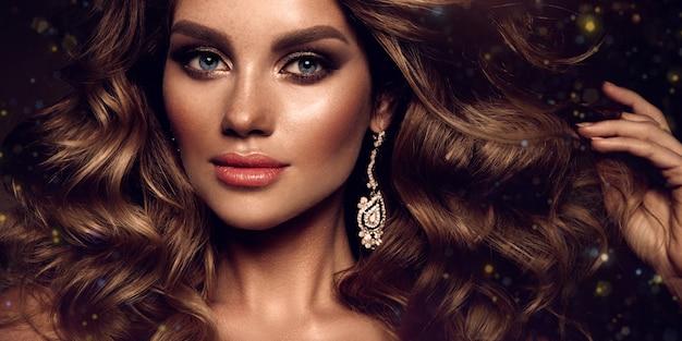 Schöne junge brünette mit make-up und lockigem haar